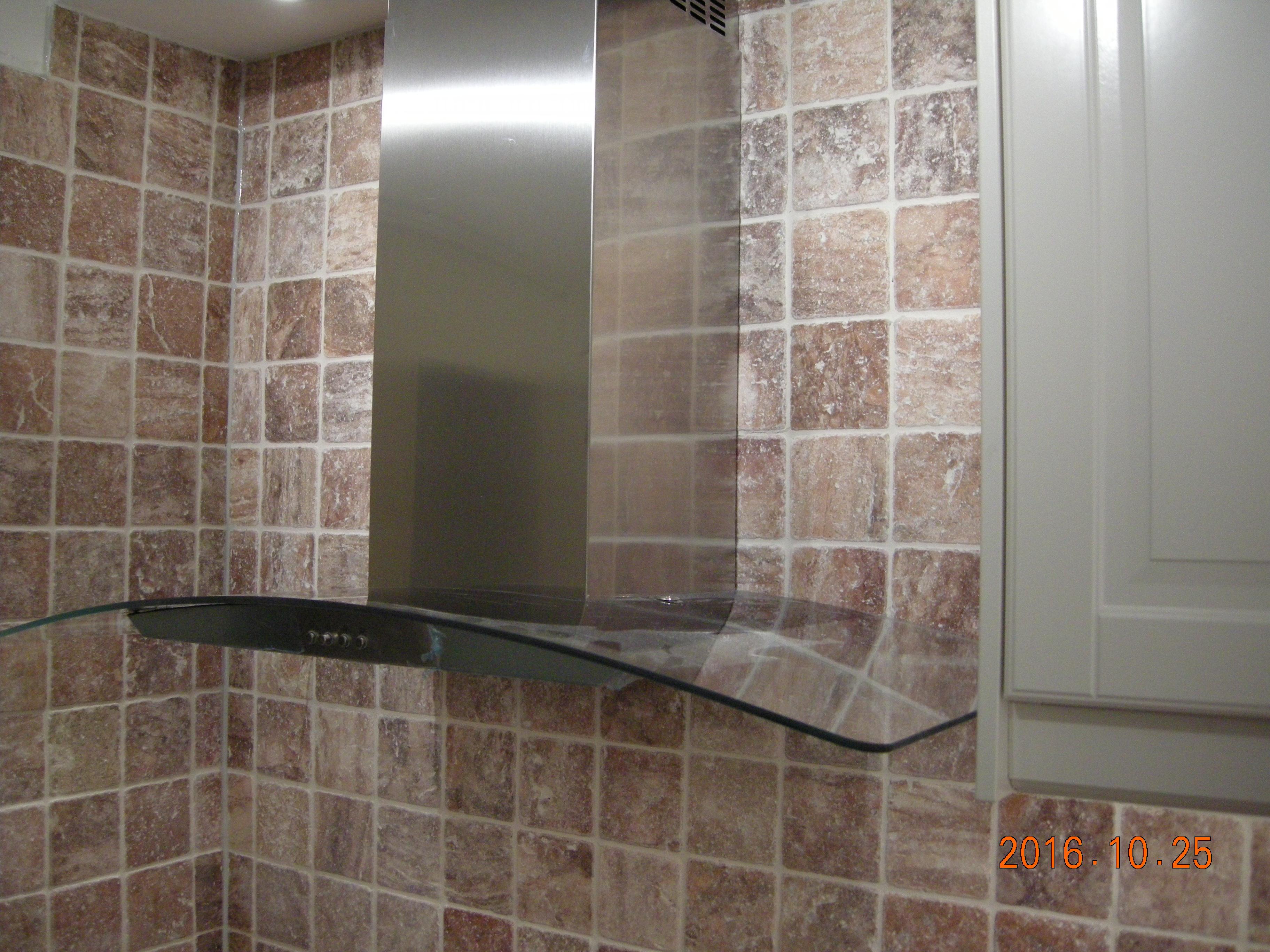 Bild med fläkt och plattsatt vägg efter köksrenovering